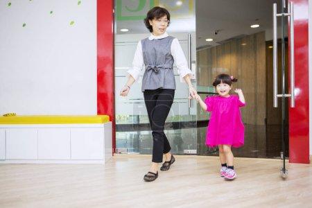 Photo pour Mère asiatique ramasser sa fille à partir d'une maternelle tout en marchant à l'extérieur - image libre de droit