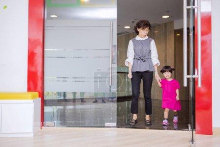 Photo pour Femme asiatique ramasser sa fille à partir d'une maternelle tout en marchant à l'extérieur - image libre de droit