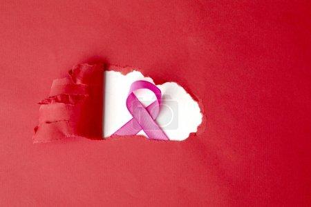 Photo pour Plan plat d'une boucle de ruban dans un trou de carton rouge déchiré, isolé sur fond blanc - image libre de droit