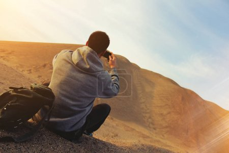 Man in the desert takes photo of dune