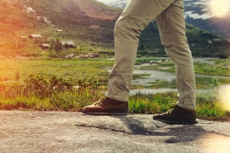 Legs traveler close-up on a background of mountain landscape