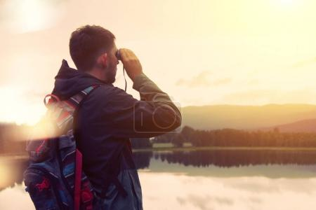 Traveler with a backpack looking through binoculars on the mountain and the lake
