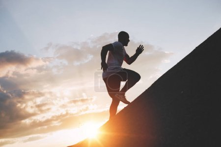 Male runner trains in an ascent to a mountain. Athlete runs through the mountains and hills at sunset