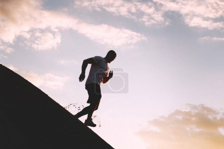 Iron man trains to a triathlon outdoors at sunset. A strong athlete runs along the hill on outdoor