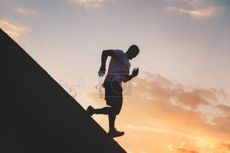 Strong man runs down a steep hill. The athlete is engaged in fitness in the evening
