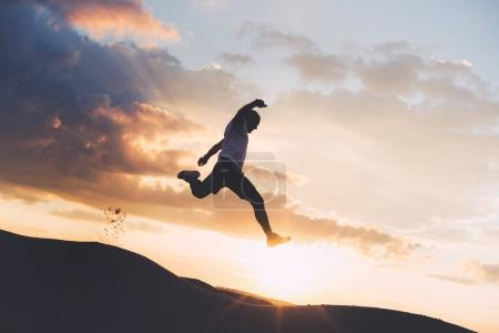 Silhouette of an extreme sportsman engaged in outdoor sports at sunset. Athlete jumping over the ravine. Intentional dark colors