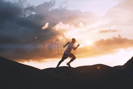 Athlete runs quickly through the hills outdoors at sunset
