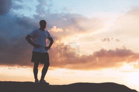 Man in sports clothes is standing on a hill after training at sunset