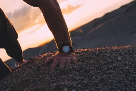 Athlete with smart watch bent to the sand after run on the hill. Smart watch close-up on an athlete's hand on background of beautiful clouds at sunset