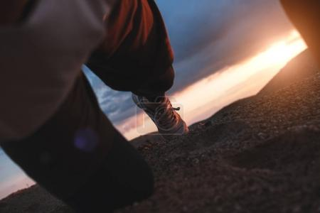 Tired athlete bent to his knees from fatigue after running. Sports shoes close-ups. Athlete in sports clothes bends to the sand and rests