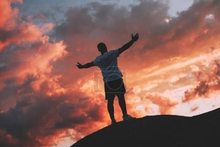 Successful and happy male athlete stands with his arms raised to the sunset