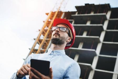 Young engineer in red hard hat with tablet in hands at construction site. Inspector with electronic tablet at construction site