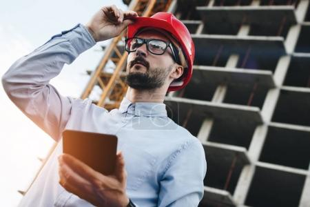 Bearded young modern engineer builder with tablet gadget in hand inspects construction of skyscraper. Concept of modern engineer and industry
