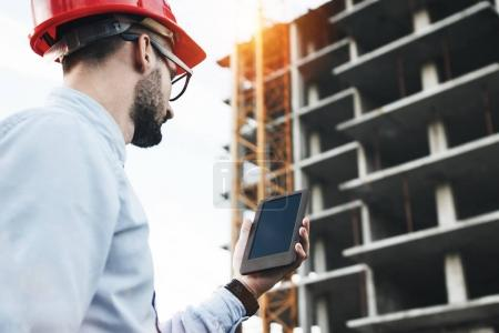 Professional male engineer with modern tablet on construction site. Modern engineer builder checks on electronic tablet schedule of work on construction of modern building