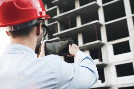 Young construction engineer in helmet checks project of building on electronic tablet. Modern builder controls construction of plant with help of gadget