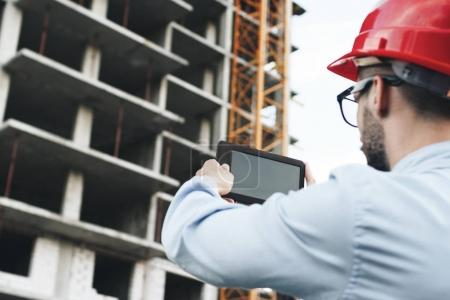 Young businessman or engineer holding modern tablet and scans building on construction. Portrait of engineer in red hard hat with gadget on construction site