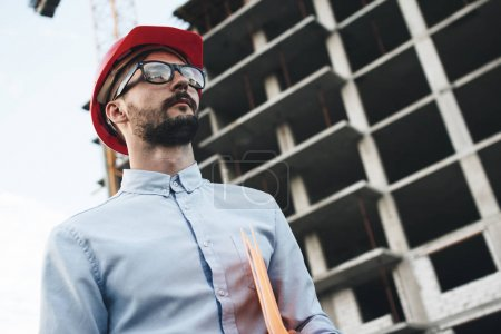 Modern business man in red hard hat holds folder with blueprint for construction industrial factory. Young bearded architect inspects construction of new building