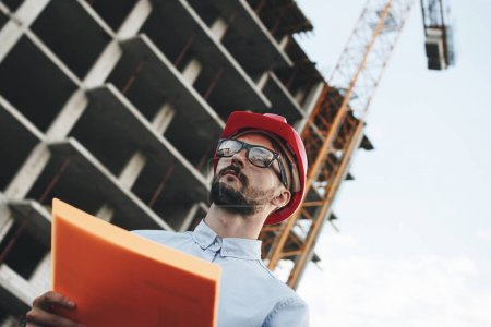 Young modern engineer builder or architect with folder of documents on background of building being built and crane. Industrial Safety Inspector checks progress of construction of industrial enterprise