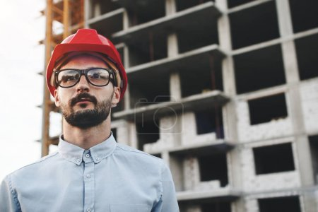 Portrait of engineer or architect wearing glasses and hard hat at construction site of new modern factory