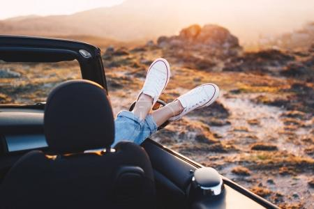 Happy woman traveler rests and admire sunset in mountains from convertible car. Woman pushes her shoes out of convertible to enjoy view and sunrise