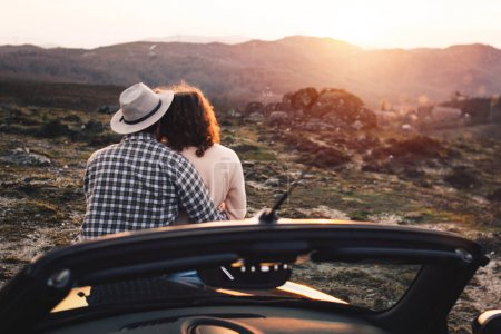 Young travelers on car rest on hood and admire view. Loving couple of hipsters watching sunset in mountains near convertible