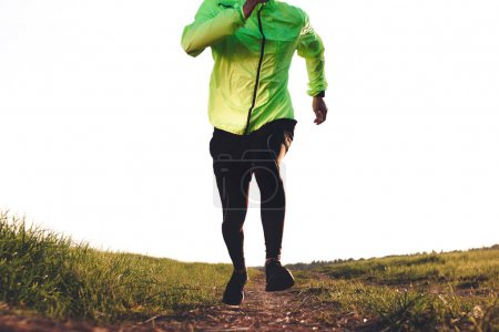 Male runner in sport clothing run fast on trail in outdoor field. Sport tight clothes. Intentional motion blur