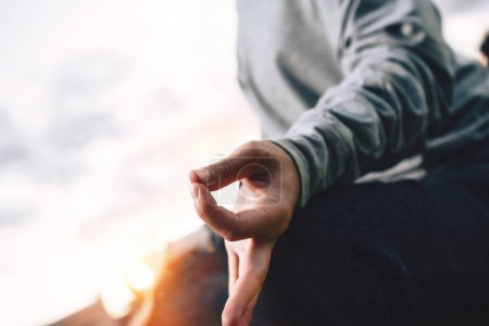 Close up of young woman meditates while practicing yoga in urban space at sunset. Concept of calmness and relax. Blurred background, flare effect