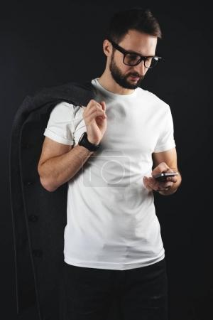 Bearded handsome hipster with coat on shoulder looks on smartphone and wearing blank t-shirt