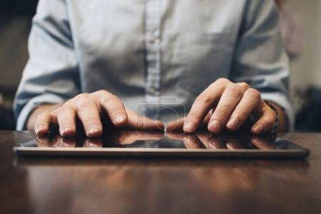 Close up view on male hands typing on screen modern tablet. Computer touch pad on wooden table