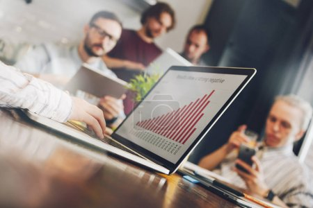 Young woman financial analyst looks at company annual report. Graph or diagram on the laptop screen. Teamwork of managers on a new project