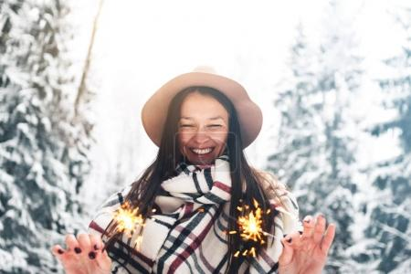 Smiling and happy pretty woman enjoying bengal light among winter forest. Girl wearing vintage hat and plaid scarf