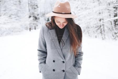 Photo pour Jeune femme heureuse et belle portant manteau et chapeau vintage marchant dans la forêt d'hiver - image libre de droit