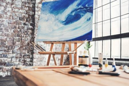 Artist's workplace in the studio. Painting on canvas on the easel in the studio