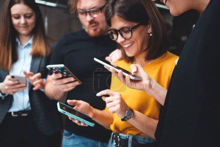Photo pour Un groupe d'adultes heureux se tient en file et utilise un smartphone moderne. Une équipe d'affaires positive tient le téléphone numérique en main - image libre de droit