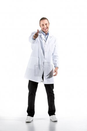 Photo for Young doctor in white coat looking at camera with thumb up isolated on white - Royalty Free Image