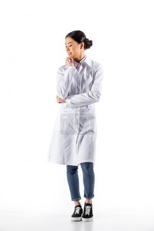 Photo pour Pleine longueur de asiatique femme médecin debout dans blanc manteau isolé sur blanc - image libre de droit