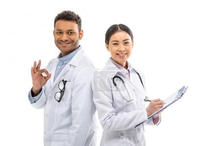 Photo for Young professional doctors standing together and gesturing isolated on white - Royalty Free Image