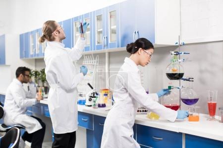 Photo pour Groupe de jeunes scientifiques professionnels faisant des expériences en laboratoire de recherche - image libre de droit