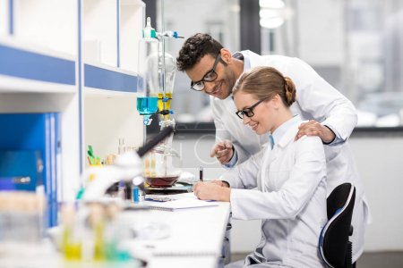 Photo pour Vue latérale des scientifiques travaillant en laboratoire - image libre de droit