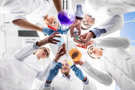 Photo pour Vue à faible angle des scientifiques tenant divers tubes à essai - image libre de droit