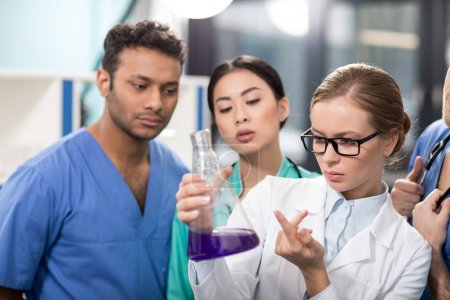 Photo for Group of medical workers analyzing test tube in laboratory - Royalty Free Image