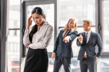 Photo for Frustrated asian businesswoman standing in office, businessmen behind gesturing and laughing - Royalty Free Image