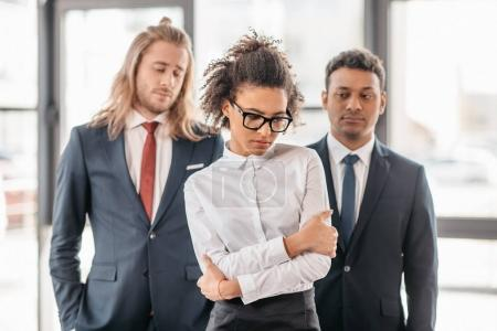 businesswoman and businessmen standing in office