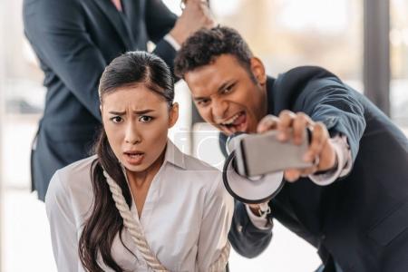 businessman taking selfie with businesswoman