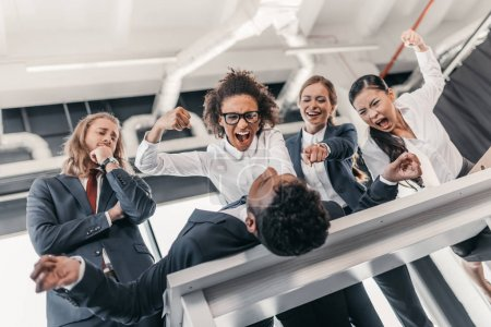 Businesswomen punishing businessman