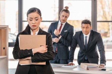 Photo for Stressed young businesswoman holding folder and businessmen standing behind - Royalty Free Image