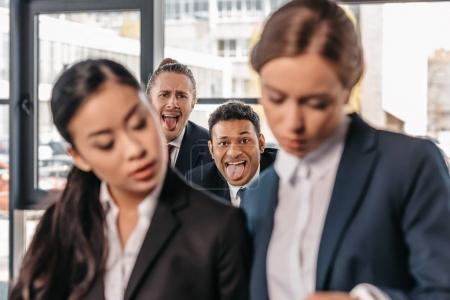 Businessmen grimacing to businesswomen