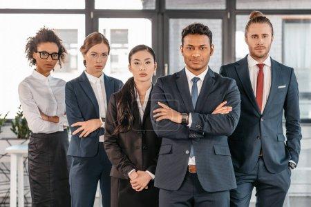 Photo pour Jeunes gens d'affaires en tenue de cérémonie posant debout au bureau moderne, équipe d'affaires multiculturelle - image libre de droit