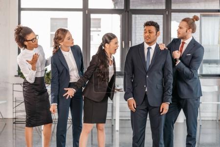 Photo pour Jeunes entrepreneurs émotionnels dans les querelles formalwear au bureau moderne, équipe d'affaires multiculturelle - image libre de droit