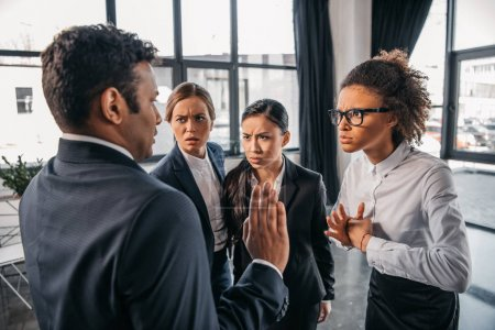 Businesspeople in formalwear quarrelling at office